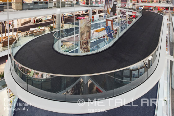 Spiral ramp featuring a filigree glass railing at Seegmüller in Pulheim by MetallArt Treppen | Staircase systems
