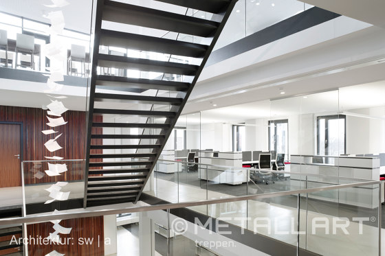 Stylish steel stairs featuring all-glass railings at WMD in Ahrensburg by MetallArt Treppen | Staircase systems