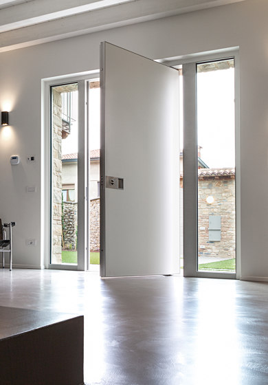 Synua | The safety door for large dimensions, with vertical pivot operation and installation coplanar with the wall. by Oikos – Architetture d'ingresso | Entrance doors